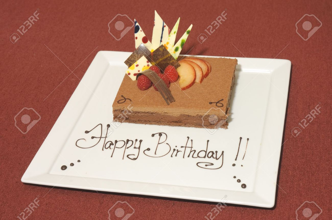 Birthday Cake Mousse On A White Plate Decorated With Chocloate And Fruit Stock Photo