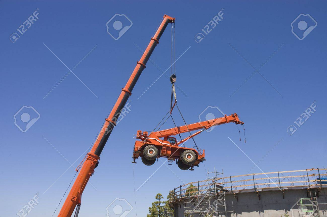 Very large crane lifting small crane from inside a concrete water
