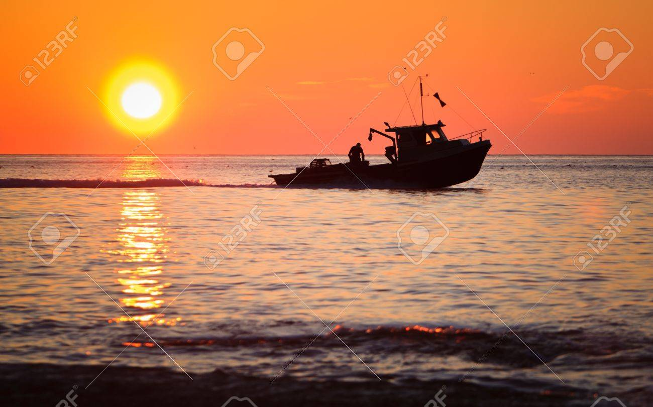 A lobster fishing boat is going to fetch his trap at early morning in Gaspesie, Quebec, Canada - 7373651