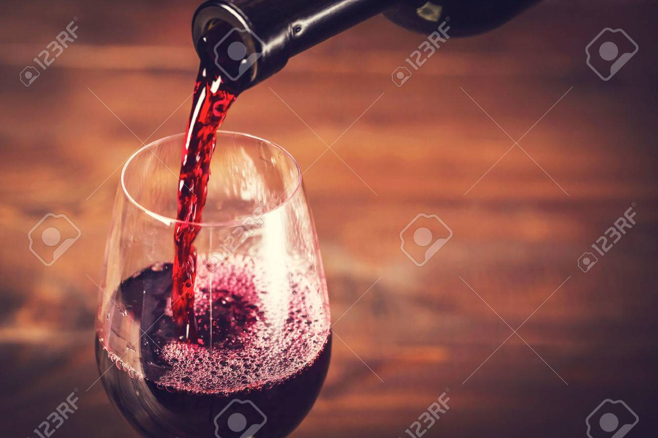 Pouring red wine into the glass against wooden background - 51975832