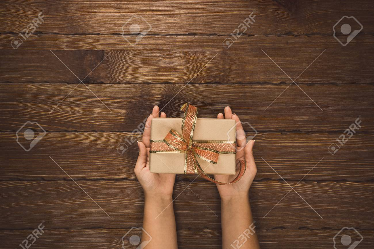 f6219cace8 Man holding Christmas presents laid on a wooden table background. Merry  Christmas greeting card.