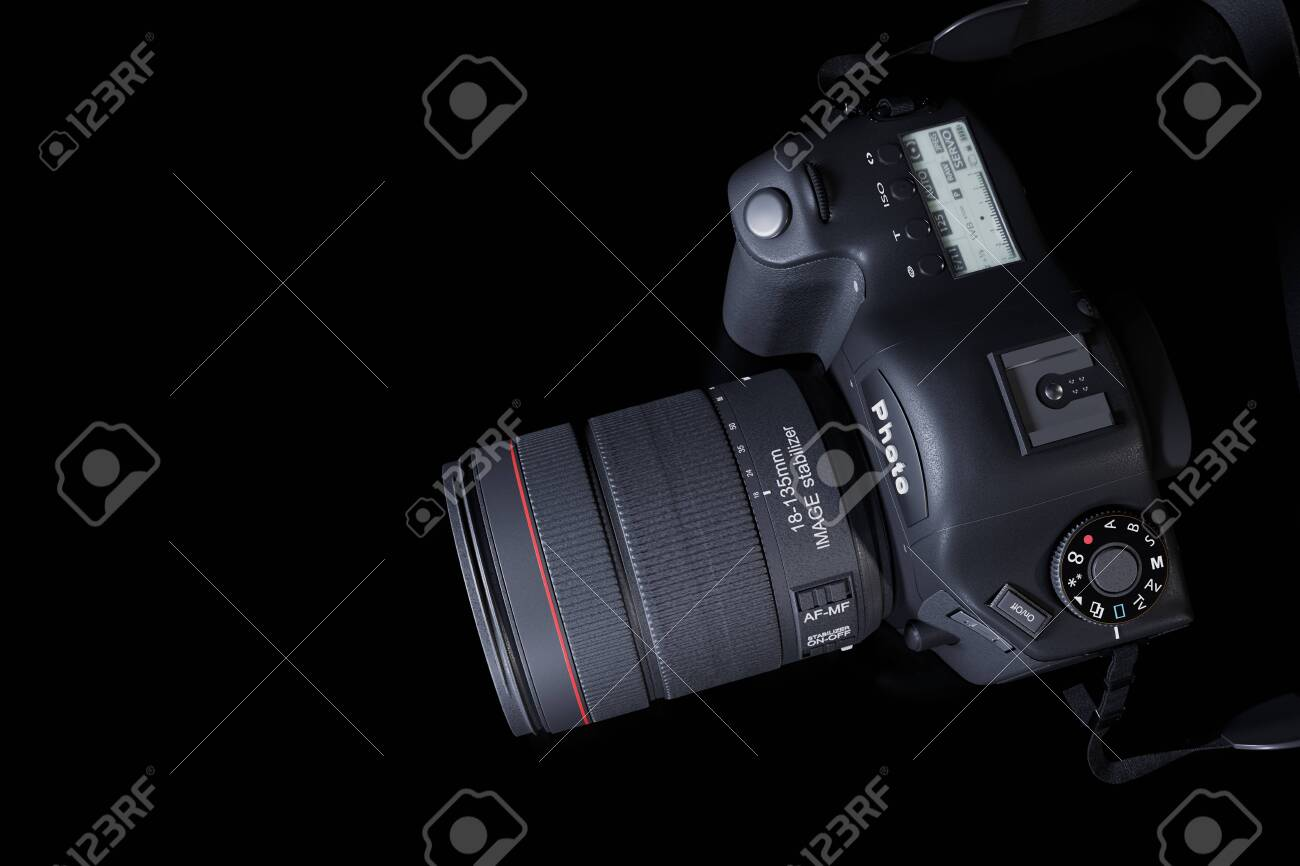 Top view professional digital camera with a zoom lens and a leather strap on a black background with copy space. View from above. Realistic 3d render. Place for advertising text. Reflection at bottom. - 149607135