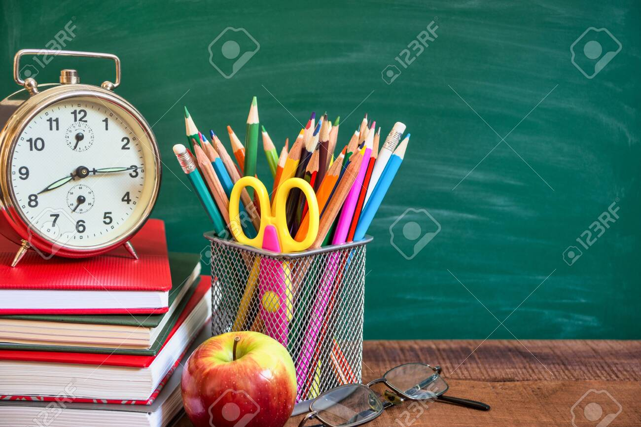 School supplies, alarm clock, apple and books on wooden table in front of the school chalkboard. Back to school concept. - 131839326