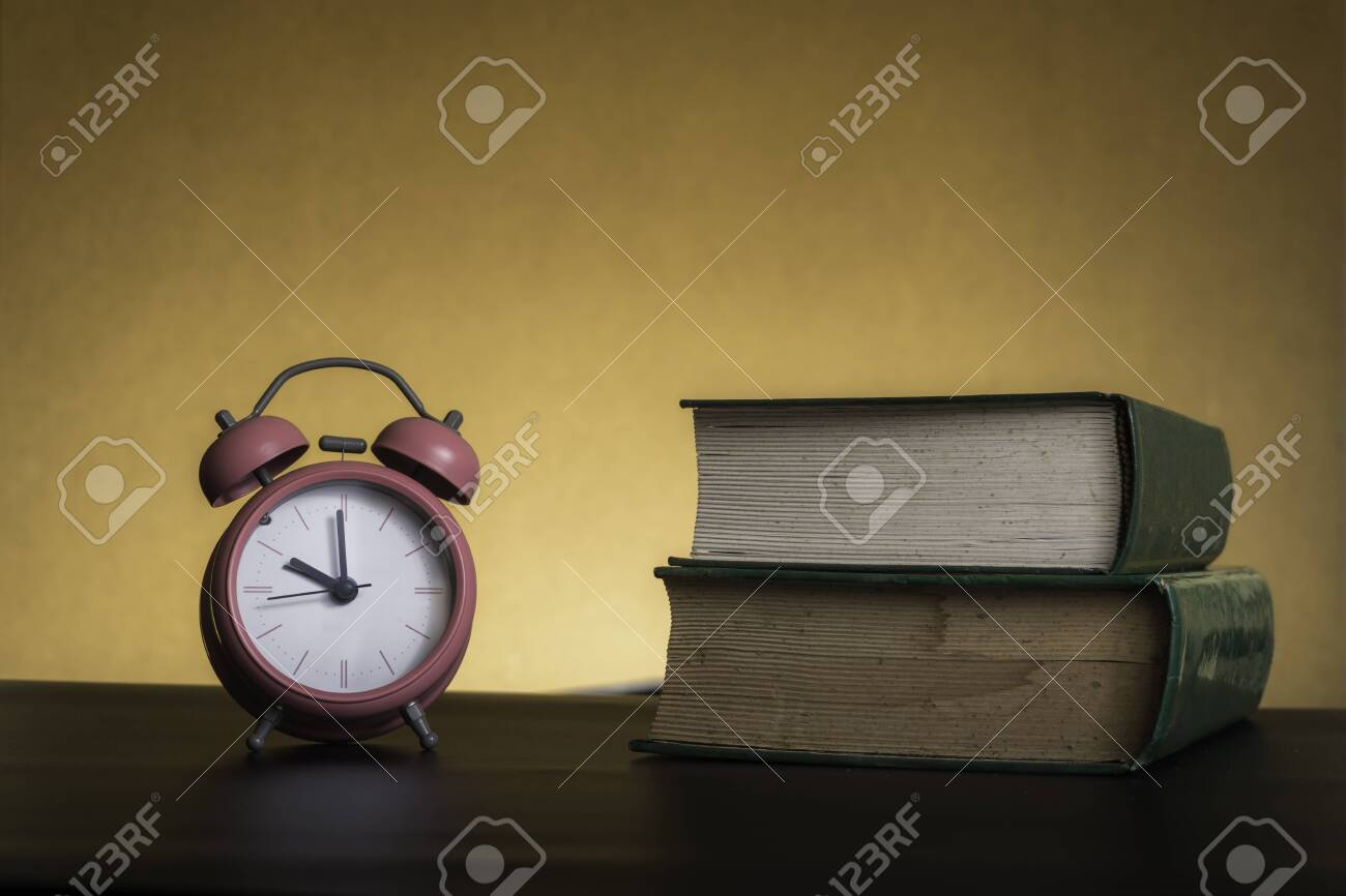 Symbolic hard study is powerful to succeed, concept with book and alarm clock. Time in business and quality - 131928744