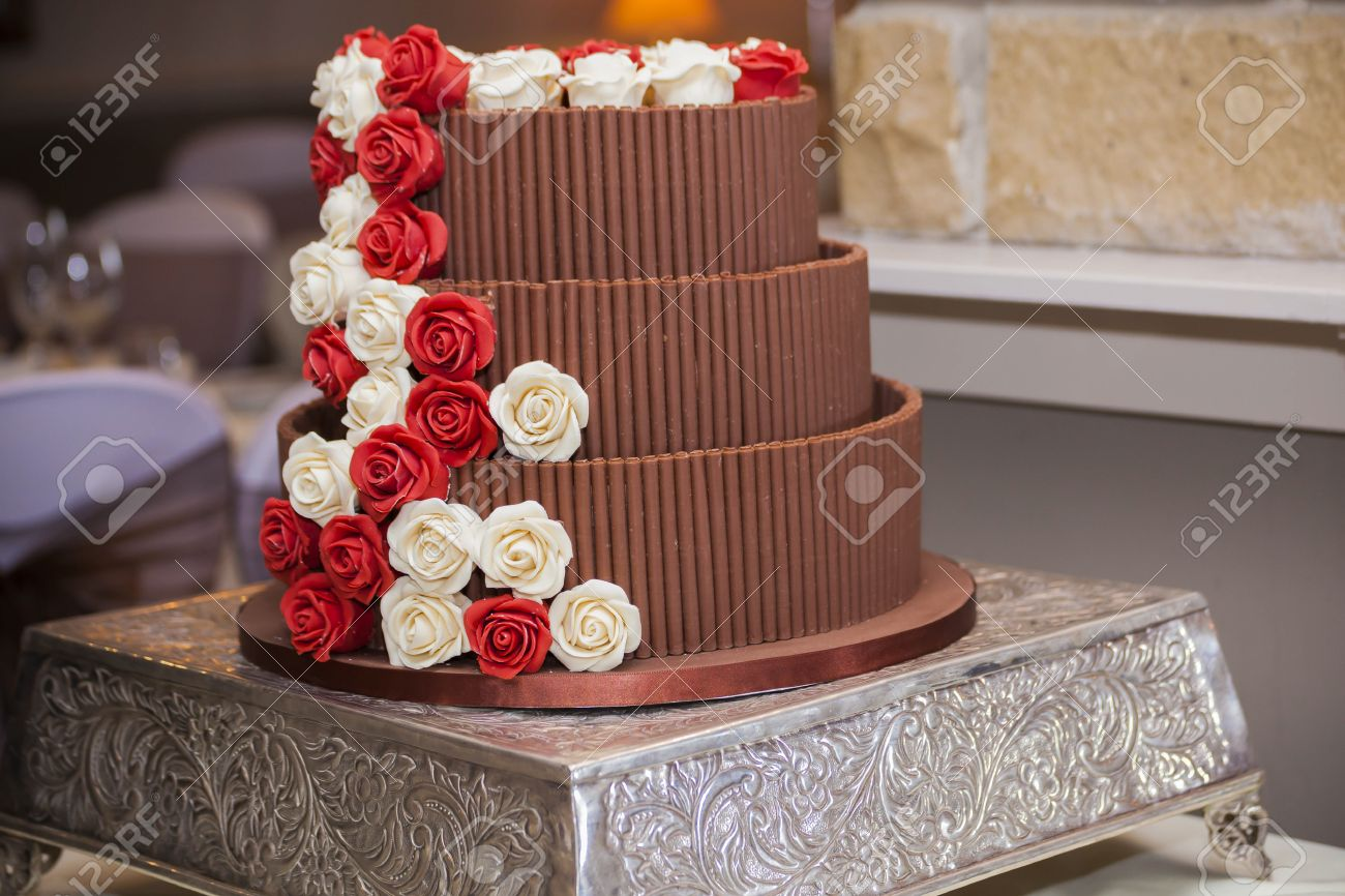 Chocolate Wedding Cake With Red And White Sugar Roses On A Silver Platter Stand Stock