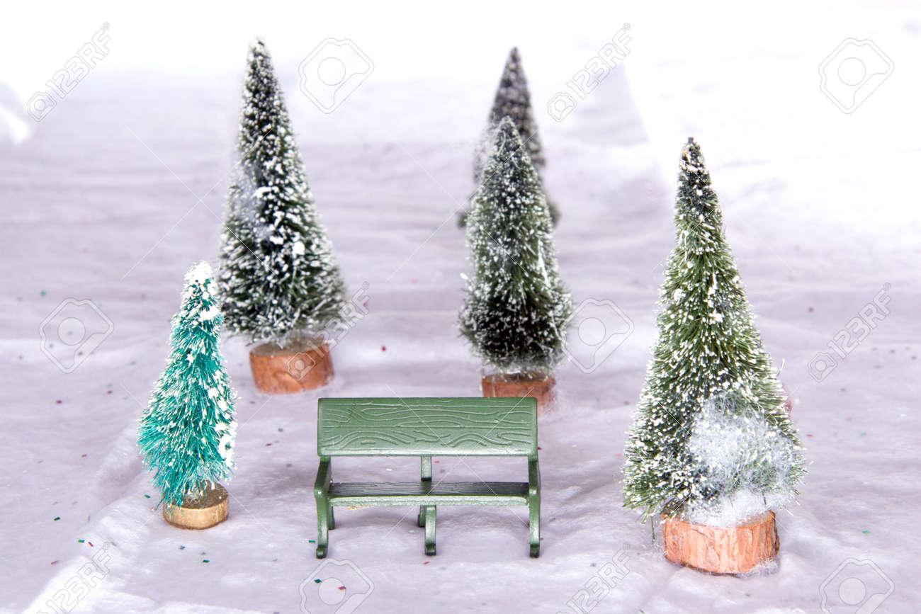 banca del parque en miniatura con rboles cubiertos de nieve de navidad en la nieve de