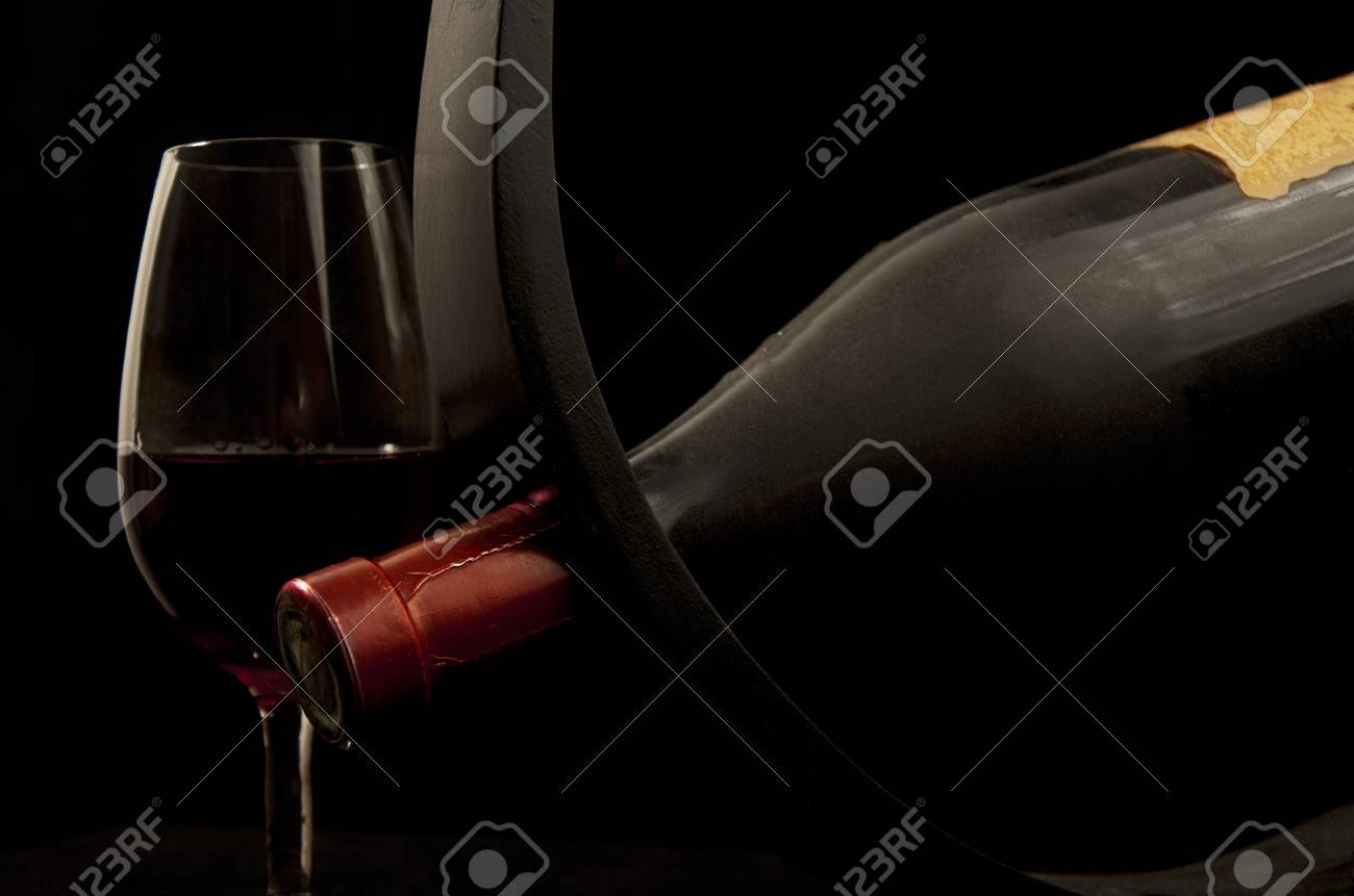 Bottle in wooden wine holder with glass of wine isolated on black Stock Photo - 11692873