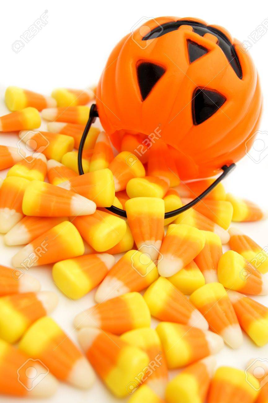 pumpkin candy holder with spilling halloween candy corn on a.. stock