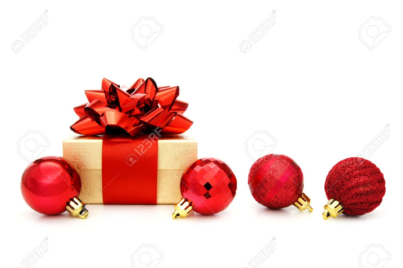 gold christmas gift box with red bow and red bauble decorations on a white background stock