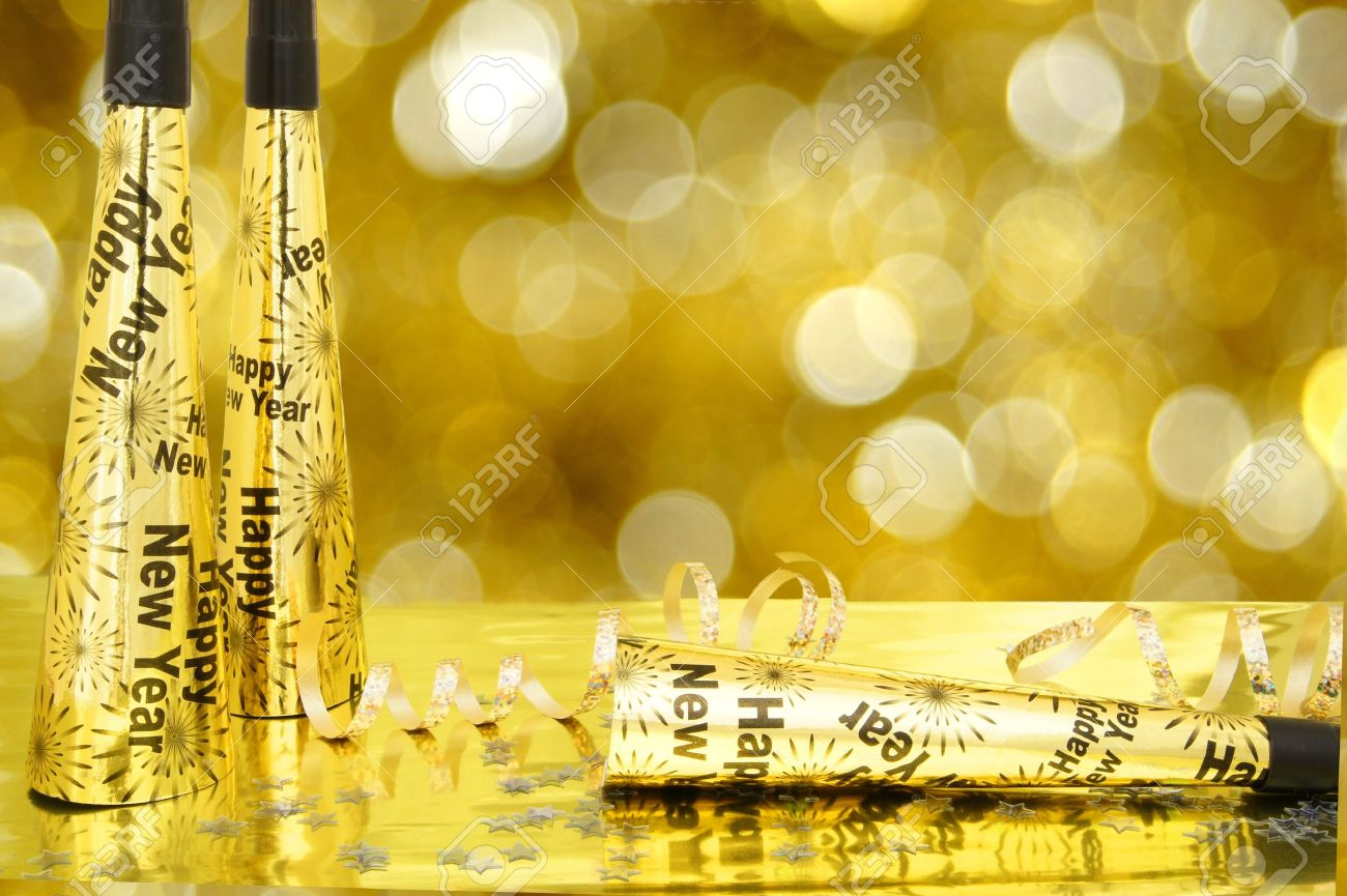 new years eve noisemakers and confetti with twinkling gold light background stock photo 16500086