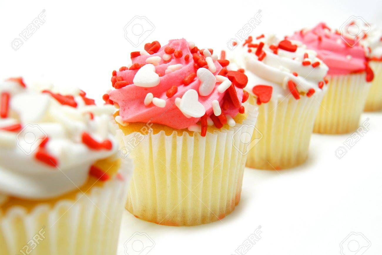Row of pink and white Valentines Day cupcakes with sprinkles over white Stock Photo - 17103333
