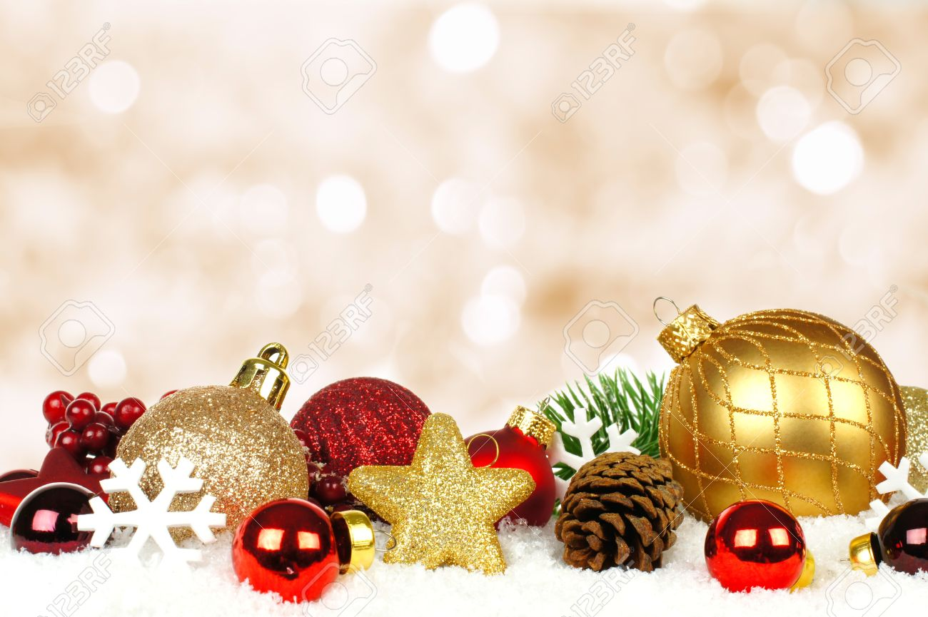 Gold and red Christmas ornament border in snow with twinkling gold light  background Stock Photo -