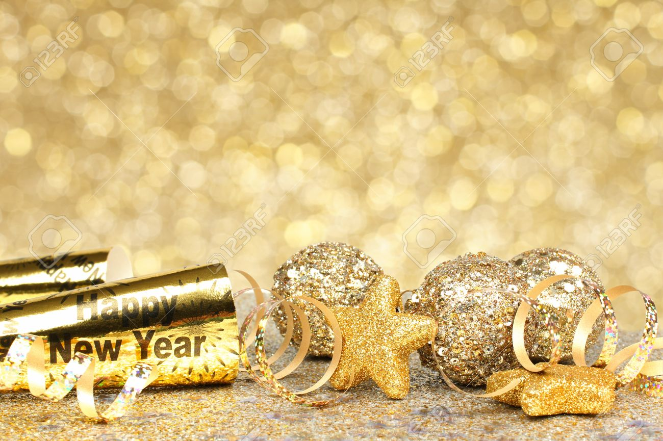 new years eve border of confetti and golden decorations on a twinkling gold background stock photo