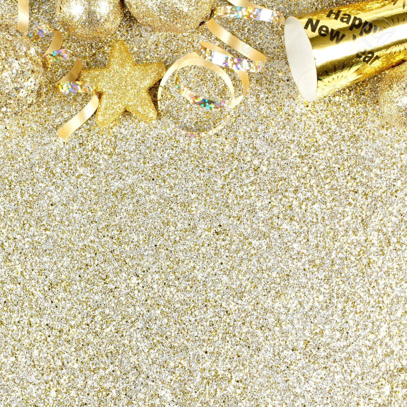 new years eve top border of streamers and decorations over a glittery gold background stock photo