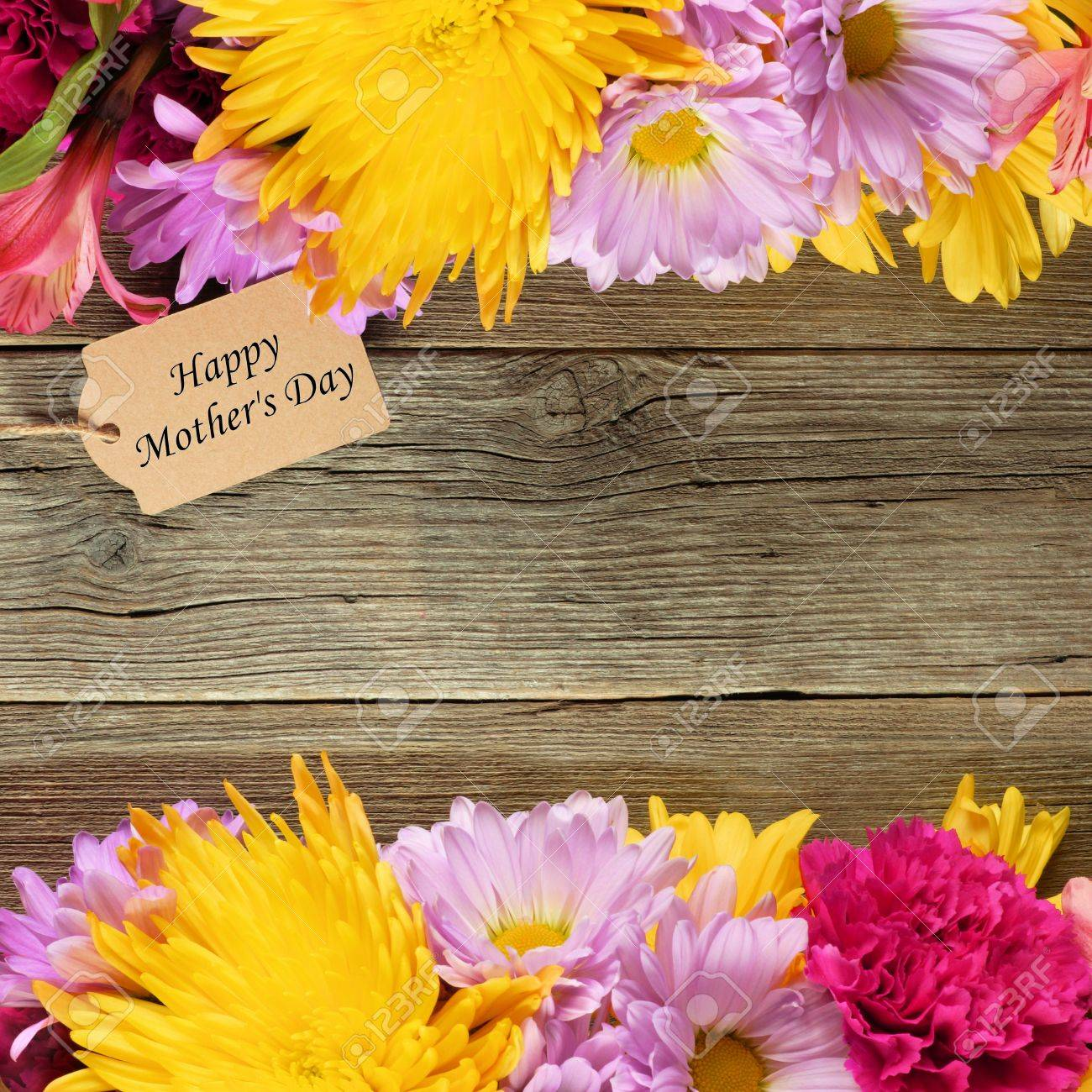 Double Border Of Flowers With Happy Mothers Day Tag Against A Rustic Wood Background Stock Photo