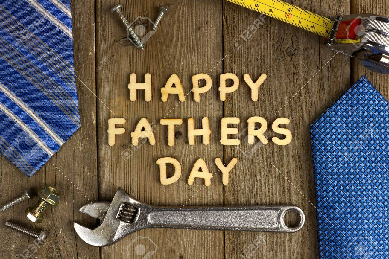 happy fathers day wooden letters on a rustic wood background with tools and ties frame stock