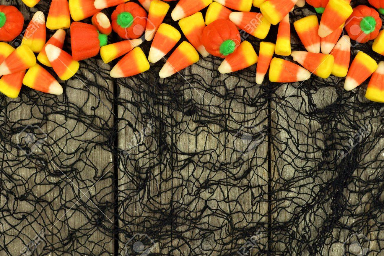 Halloween Candy Top Border Against A Rustic Wood And Spooky Black Cloth Background Stock Photo