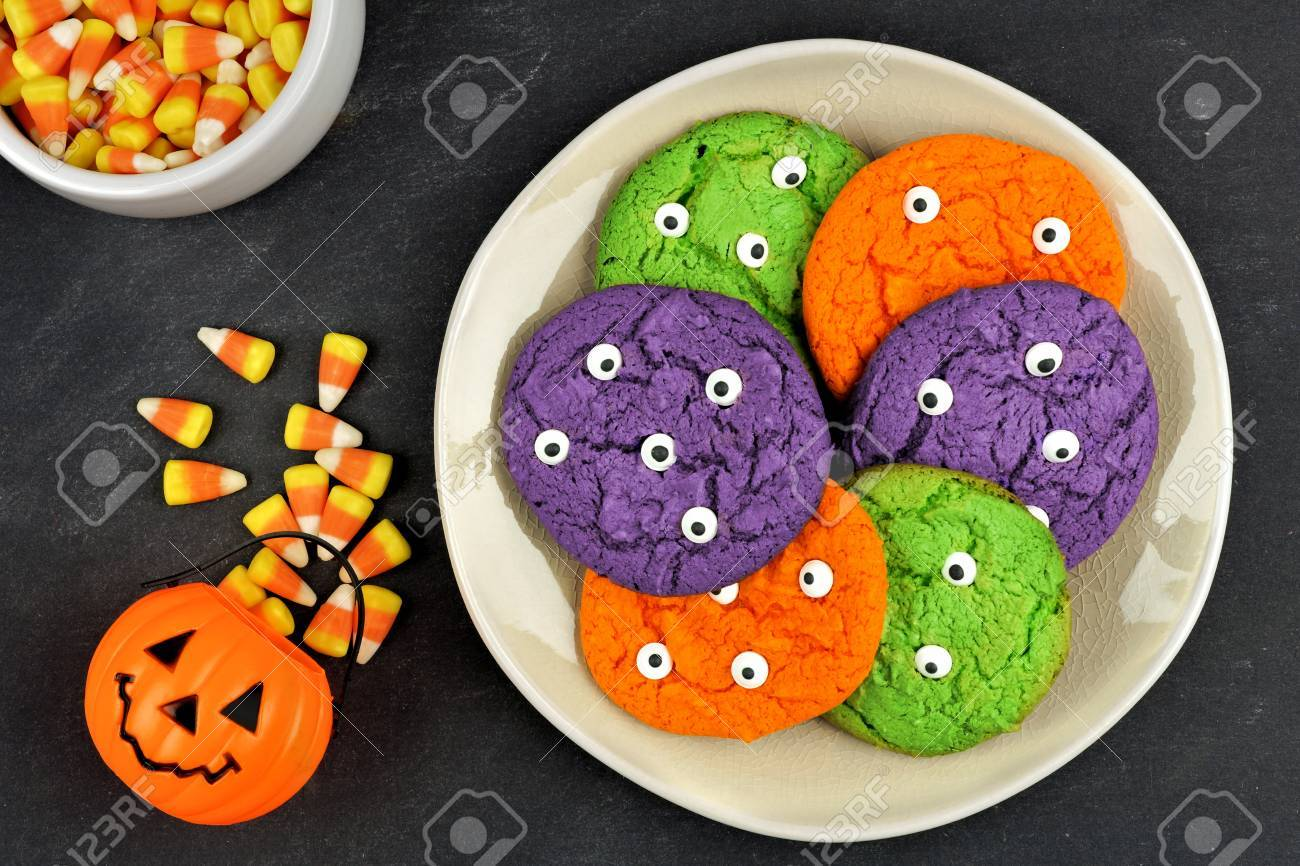 colorful halloween monster eyeball cookies on a plate against a black slate background with candy corn