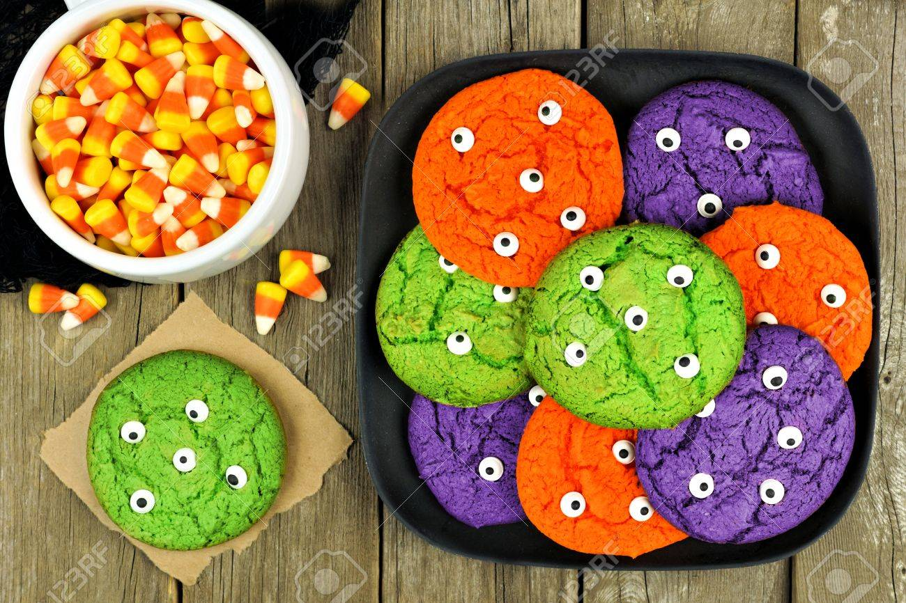 colorful halloween monster eyeball cookies on a black plate against rustic wooden background with candy corn