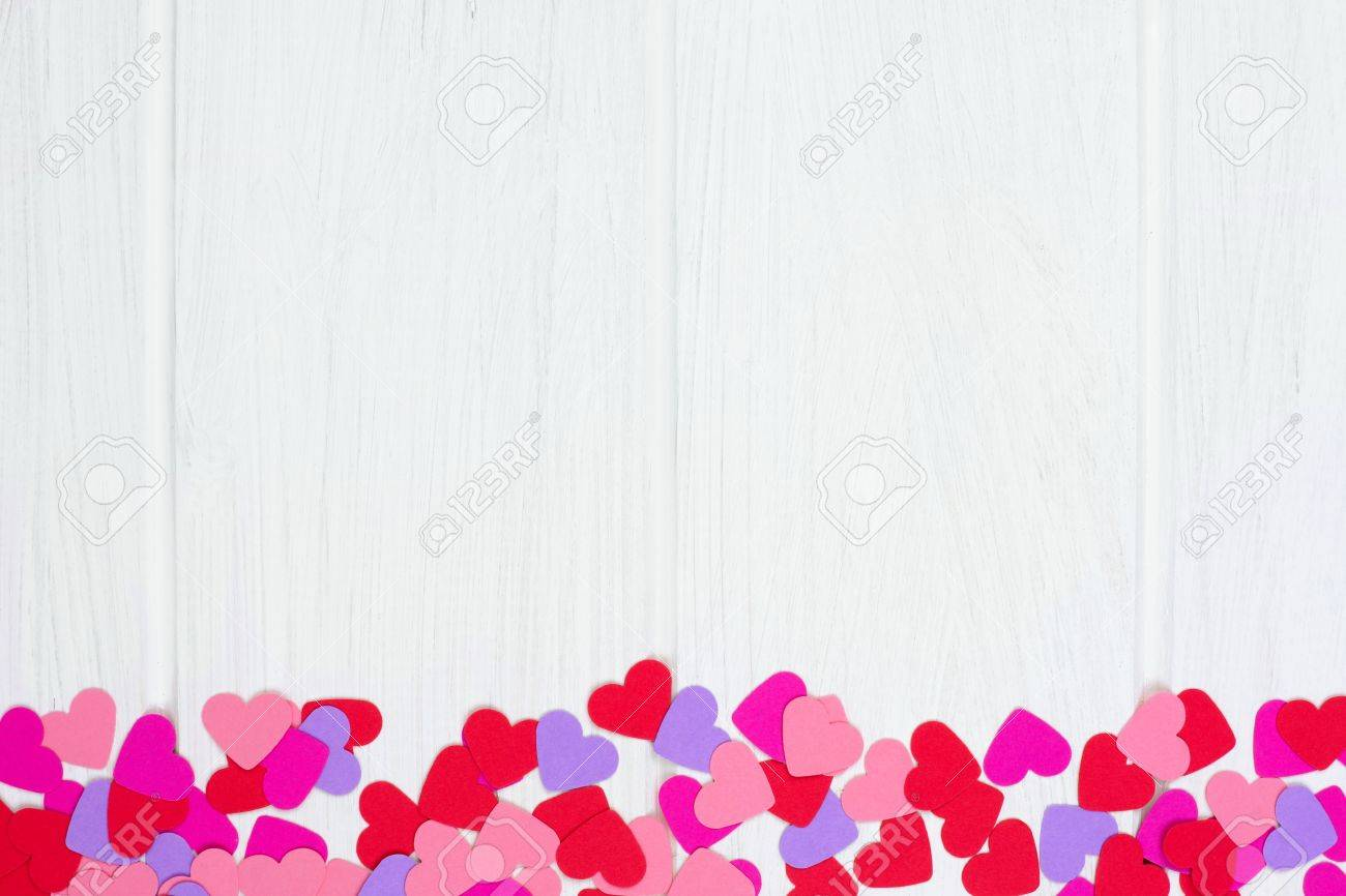 Bottom Border Of Colorful Valentines Day Paper Hearts Against A White Wood  Background Stock Photo