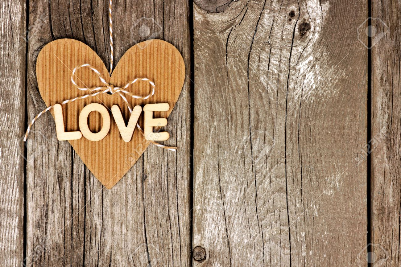 Rustic Heart Shaped Gift Tag With LOVE Wood Letters Hanging Against A Vintage Wooden Background Stock