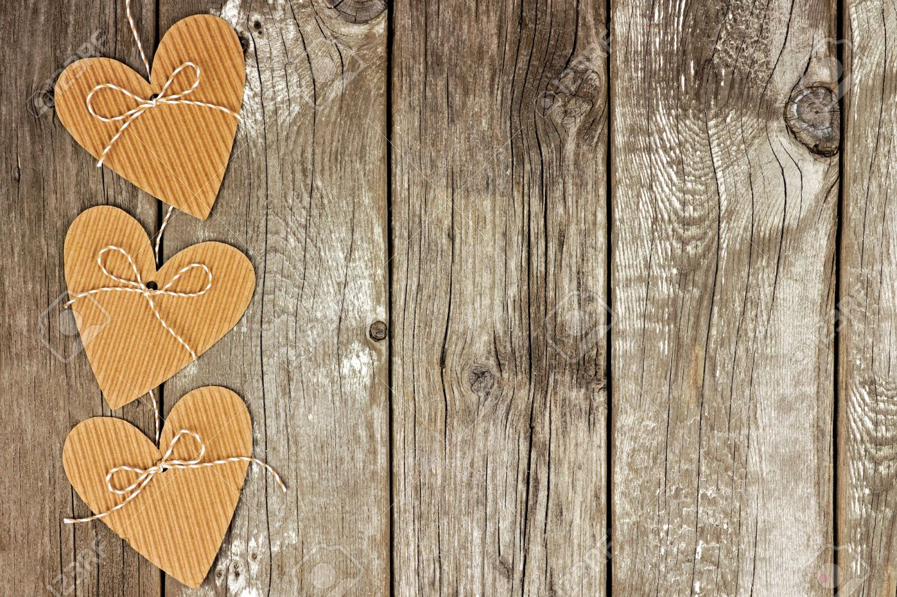 Side Border Of Rustic Heart Shaped Cardboard Gift Tags Against A Vintage Wood Background