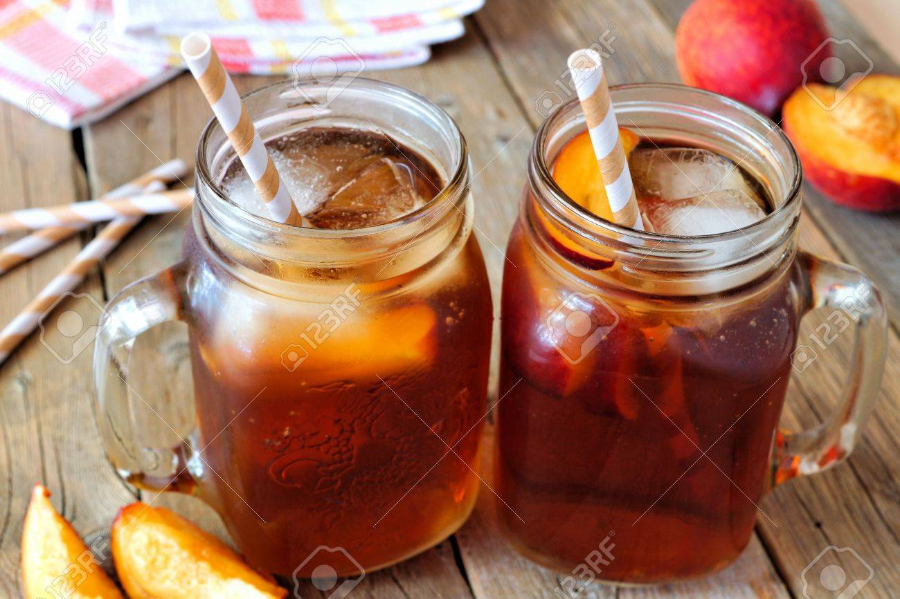 Two Mason Jar Glasses Of Homemade Peach Iced Tea On A Rustic Stock