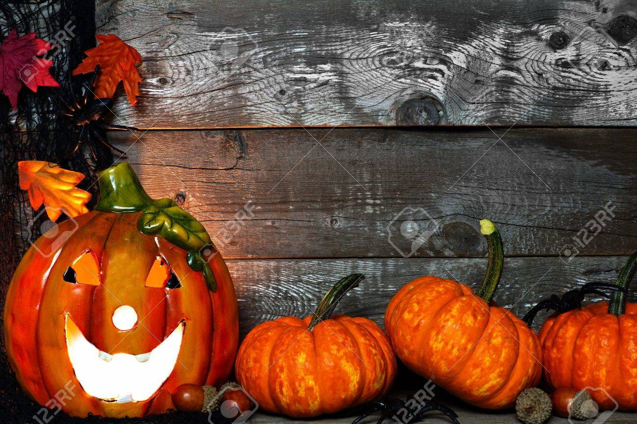 Lit Halloween Jack O Lantern With Pumpkin Corner Border Against A Rustic Old Wood Background Stock