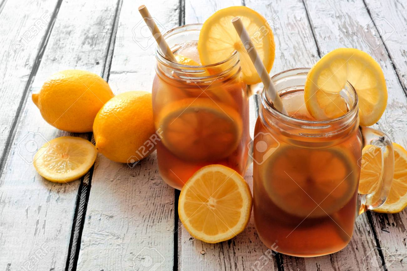 Two Mason Jar Glasses Of Homemade Iced Tea On A Rustic White Stock