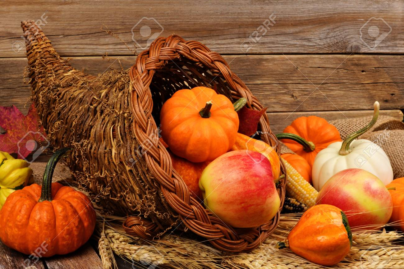 Thanksgiving cornucopia filled with pumpkins and fruit against a rustic wooden background - 87005235