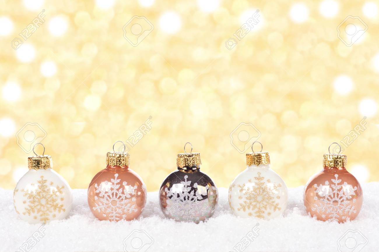 White And Gold Christmas Ornaments In Snow With Twinkling Gold