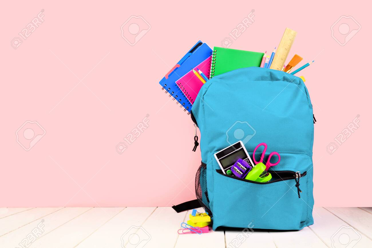 Blue backpack full of school supplies against a pink background, back to school concept - 126663813