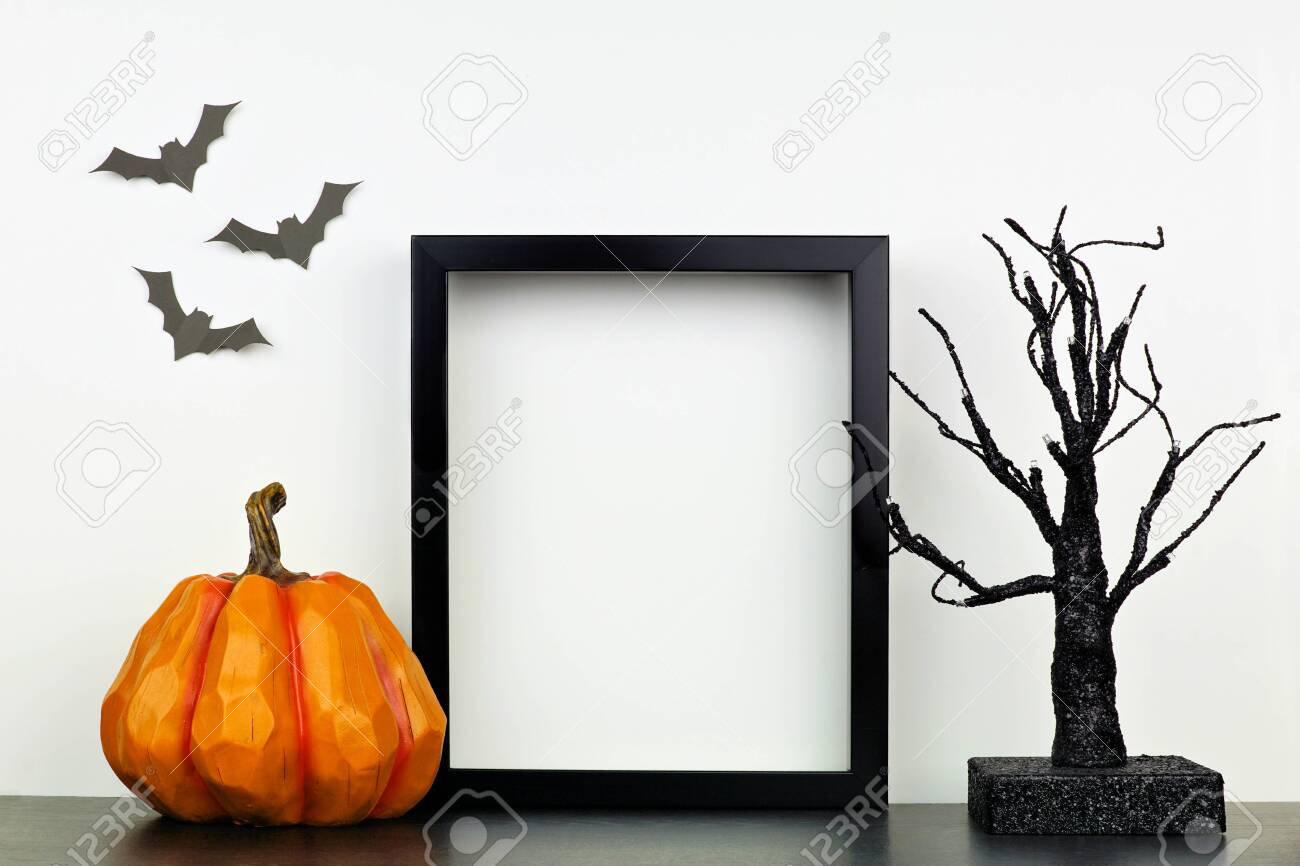 Mock up black frame with Halloween pumpkin and spooky tree decor on a shelf against a white wall - 130017182