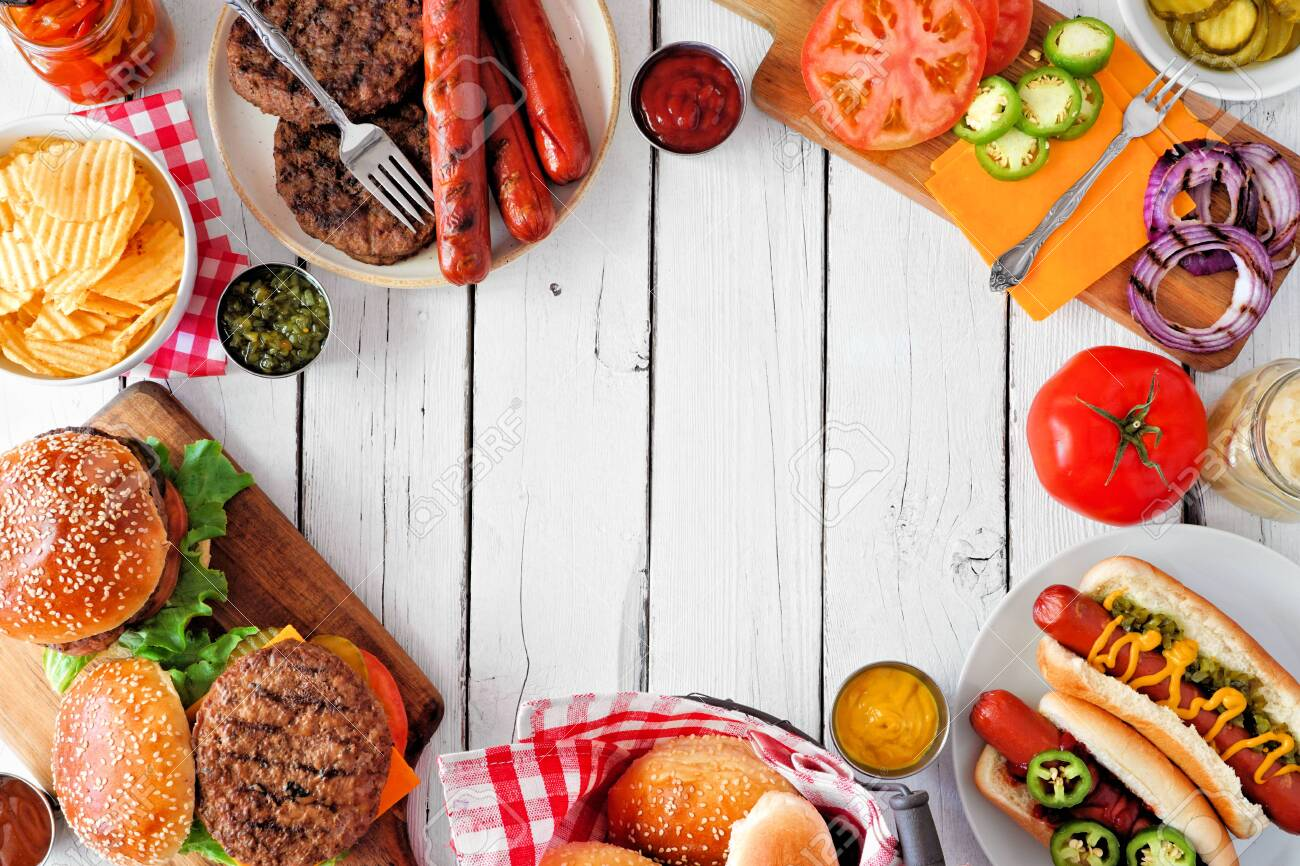 Summer BBQ food frame with hot dog and hamburger buffet, overhead against a white wood background - 150438480