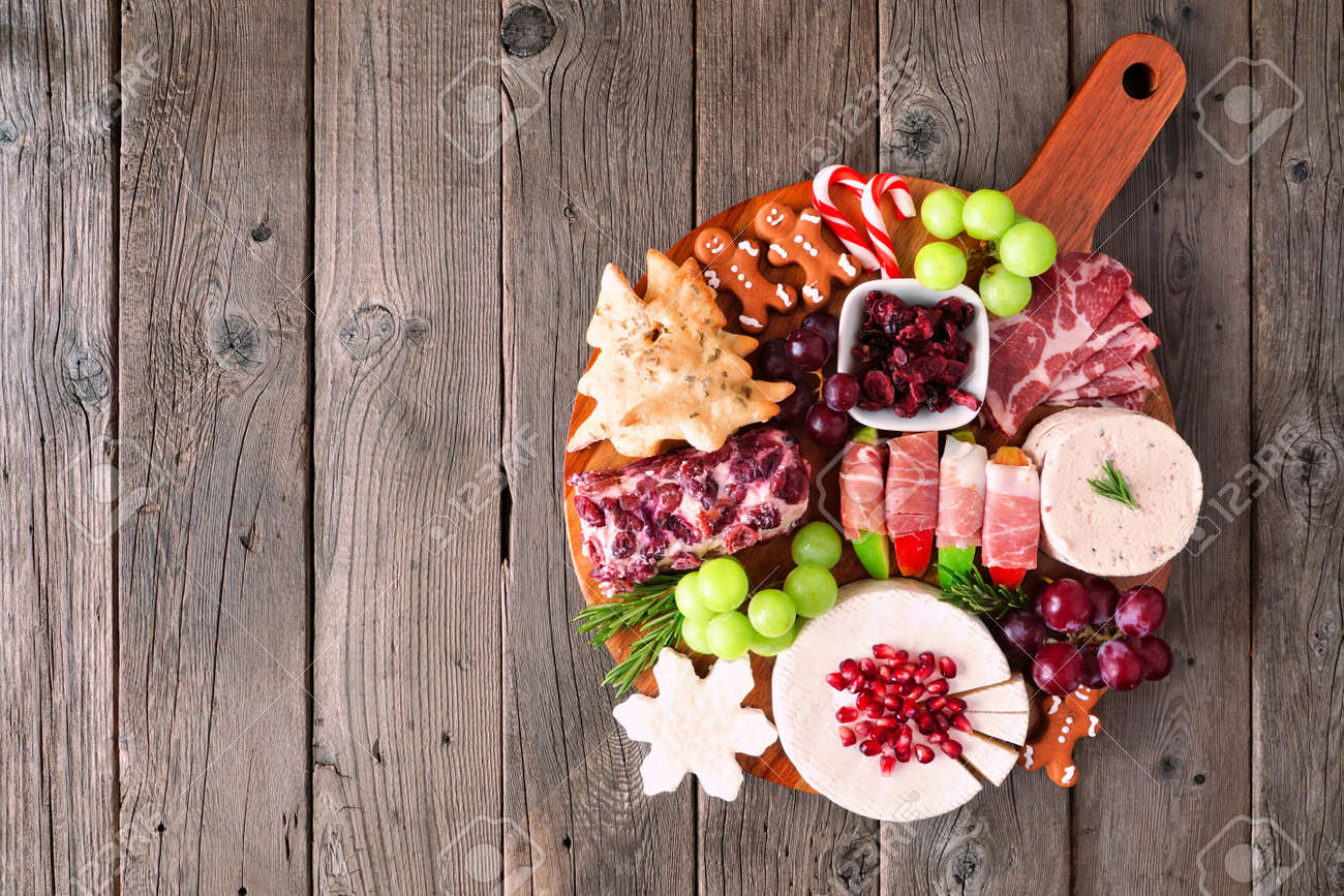 Christmas theme charcuterie board. Overhead view against a dark wood background. Mixed cheese and meat appetizers. - 157824891