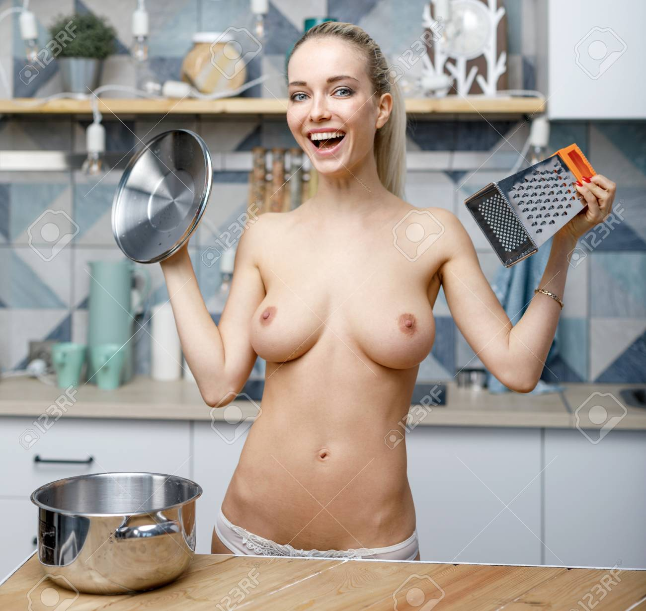 Happy Nude Woman In The Kitchen