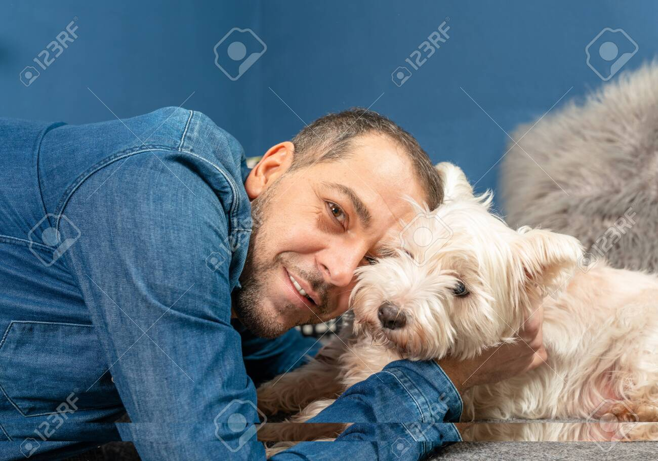 A man cuddles with his dog on the couch - 143720543