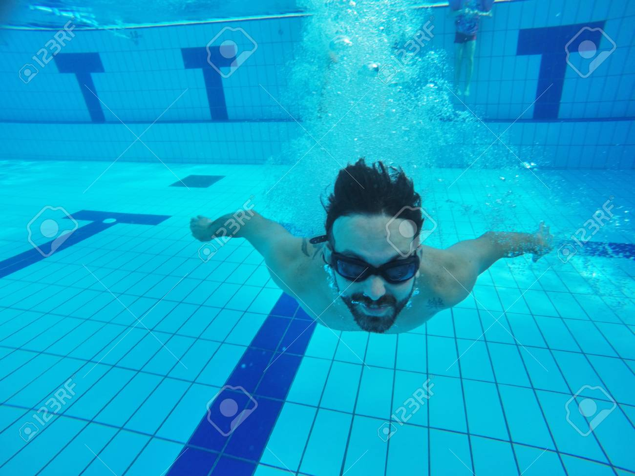 Fit swimmer training in the swimming pool. Professional male..