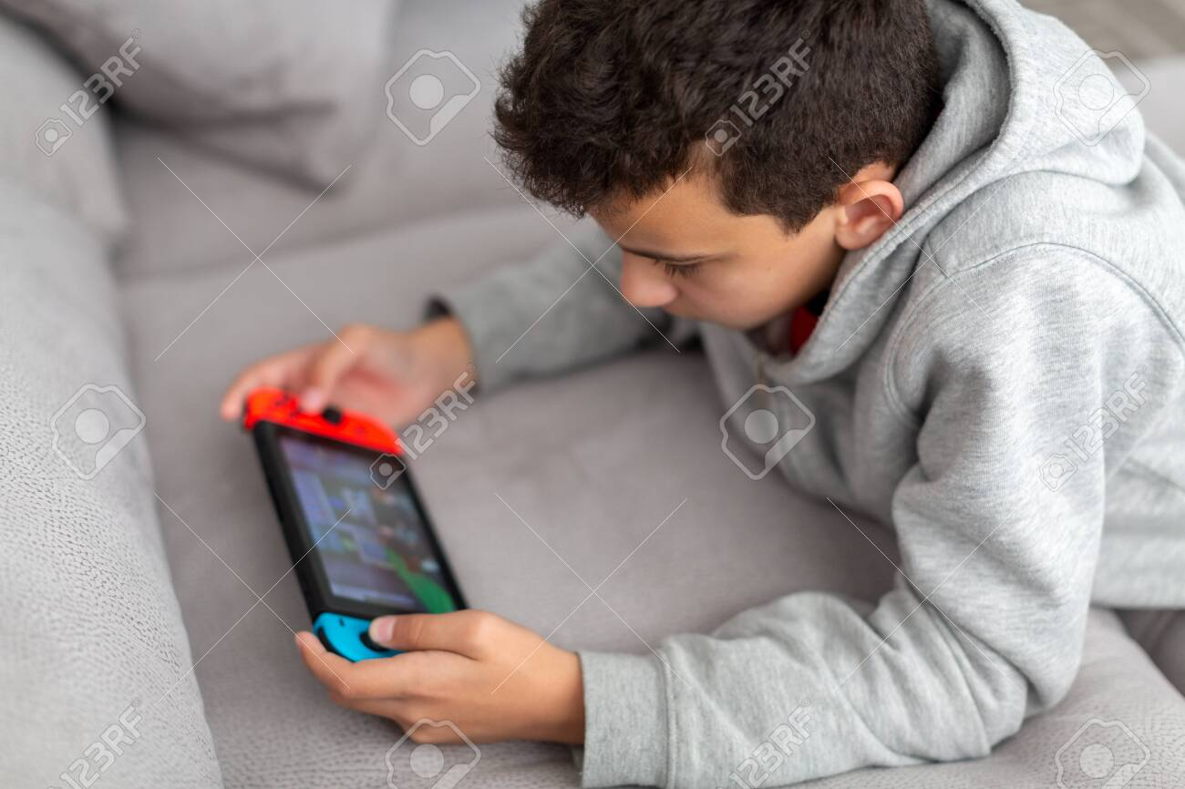 Teenager lies on a sofa and plays a game. He has a portable game console in his hands. How teens spend their vacations. - 138244224