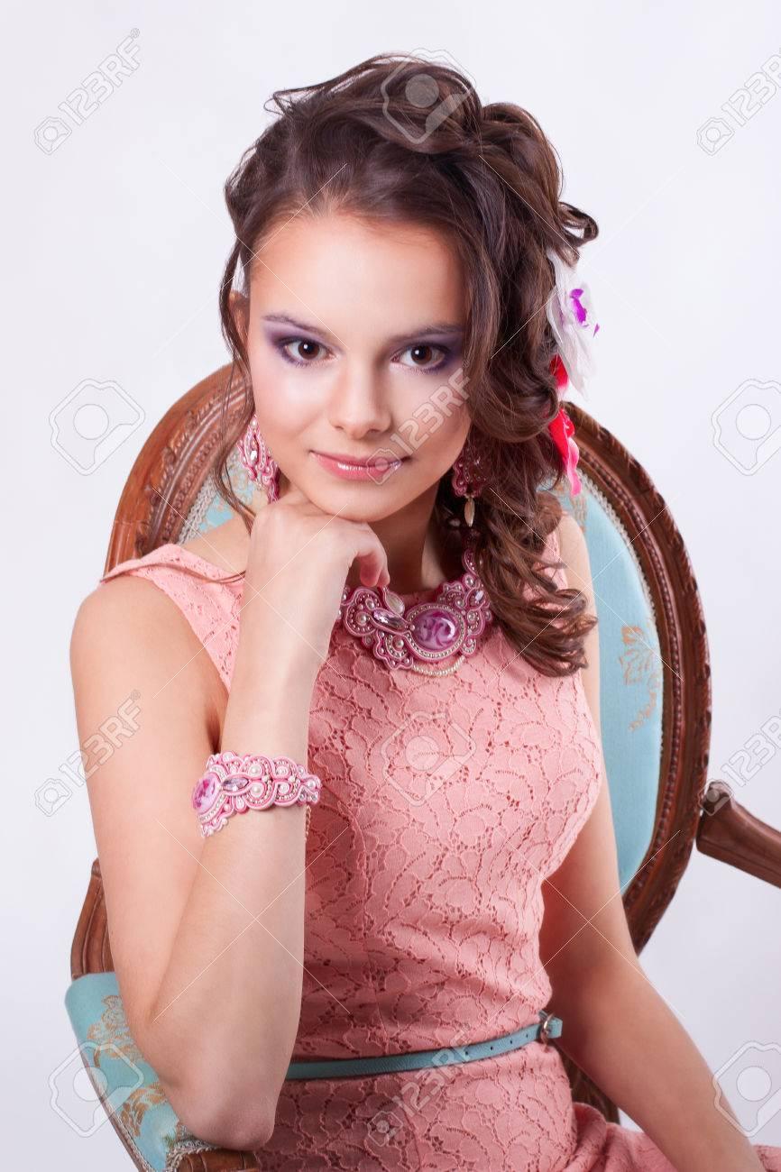11a4c0444 ... Con Maquillaje De Color Púrpura En Vestido Rosa Con Decoraciones  Soutache Técnica Con Flores En El Pelo En Un Fondo Blanco. Chica Sentada En  Una Silla ...