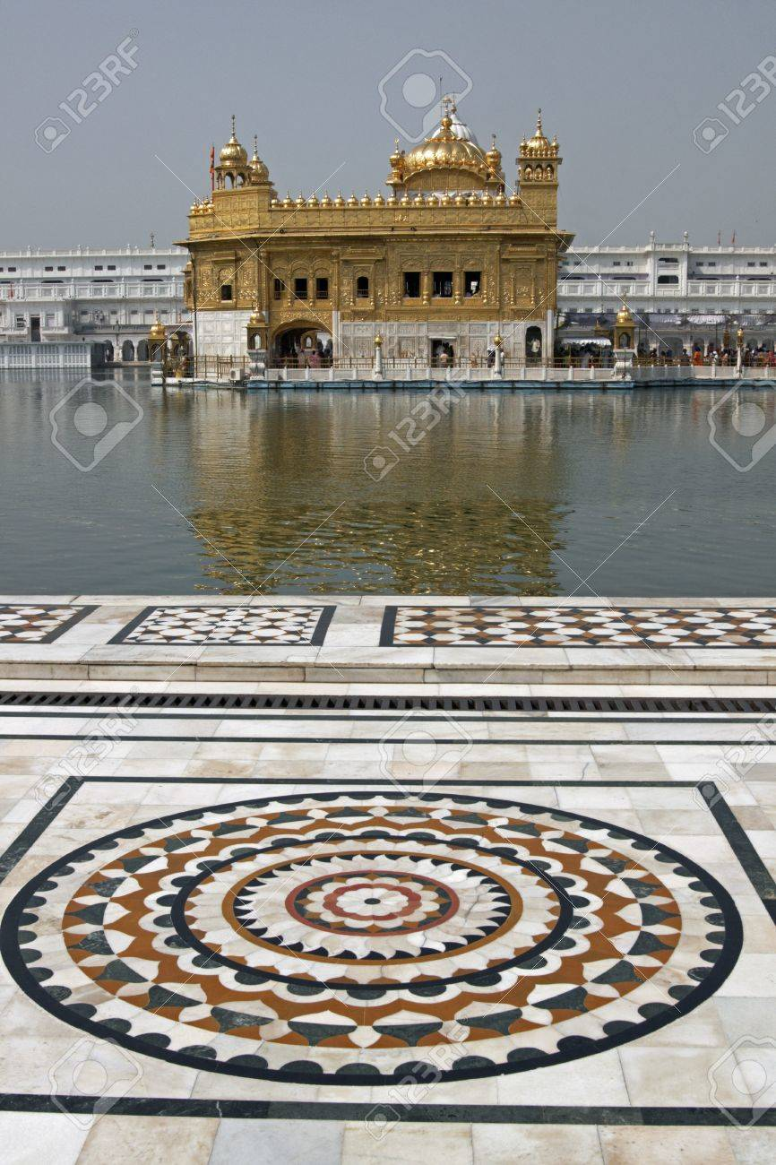 Golden Temple. Holiest shrine of the Sikh religion. Ornate marble around the pool of water containing an ornate building covered in gold. Amritsar, Punjab, India. Standard-Bild - 4460005