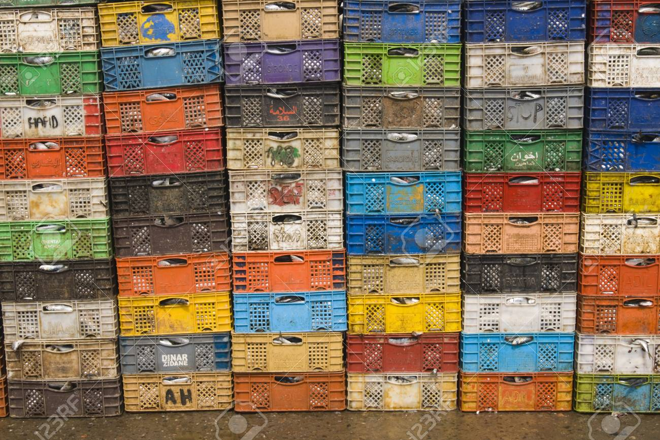 Essaouira, Morocco - August 28, 2009: Stack of colorful packing cases containing recently landed fish in the fishing village of Essaouira, Morocco. Stock Photo - 8626253
