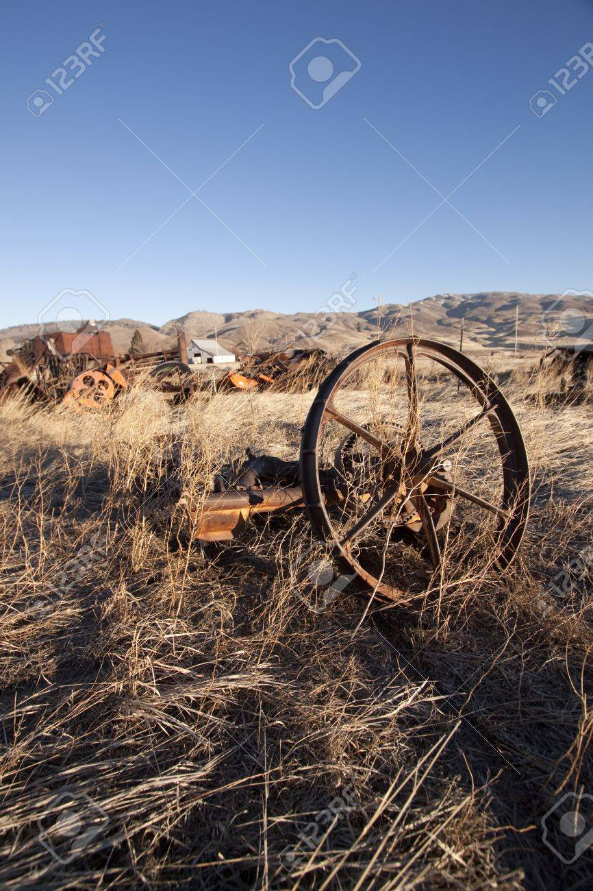 old rusty farm equipment in the middle of a field Stock Photo - 9895669