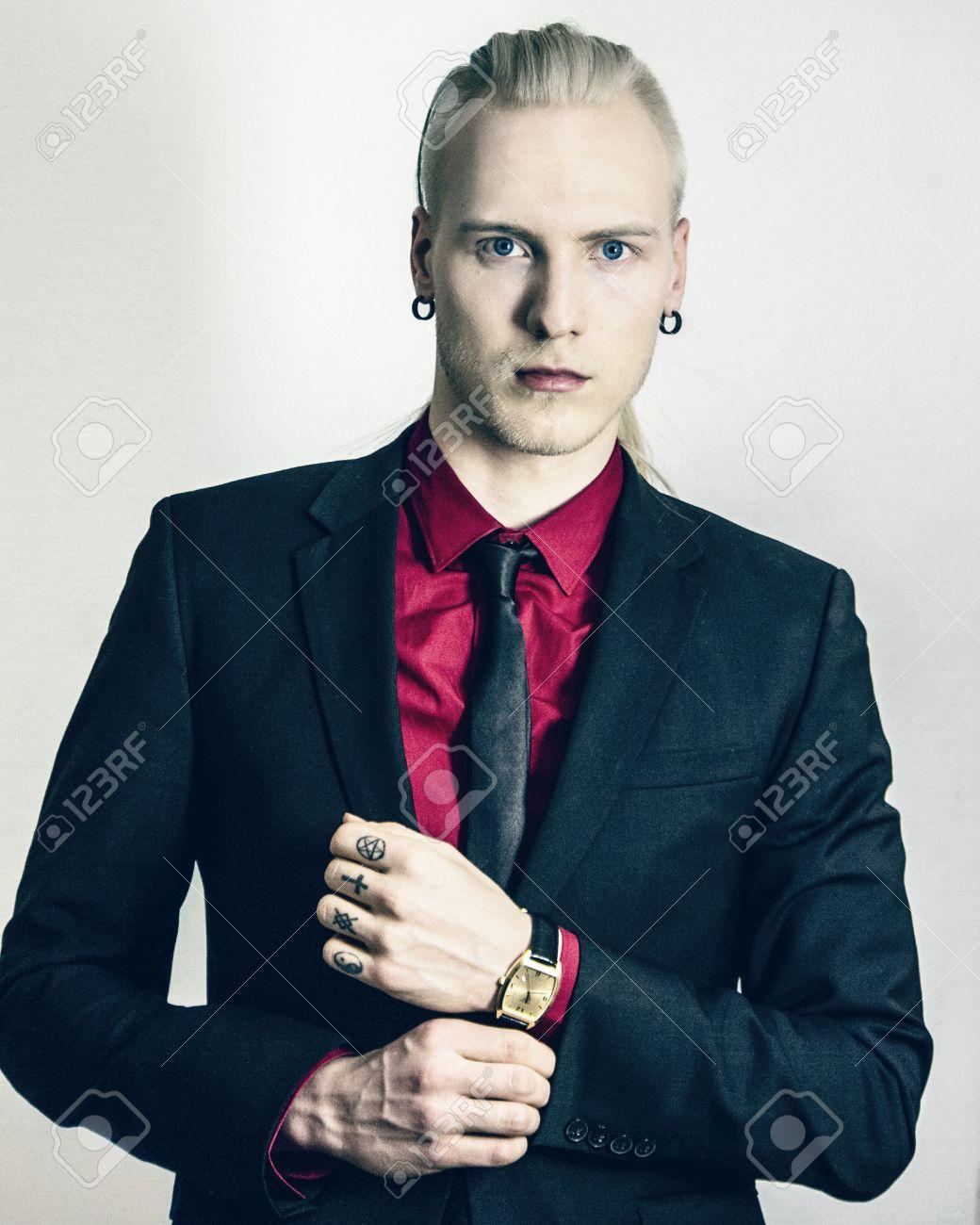 e371bb2f3 Foto de archivo - Hombre joven y elegante con un traje negro y camisa roja  que mira a la cámara y abotonarse la manga. con el reloj de oro y tatuajes  de ...