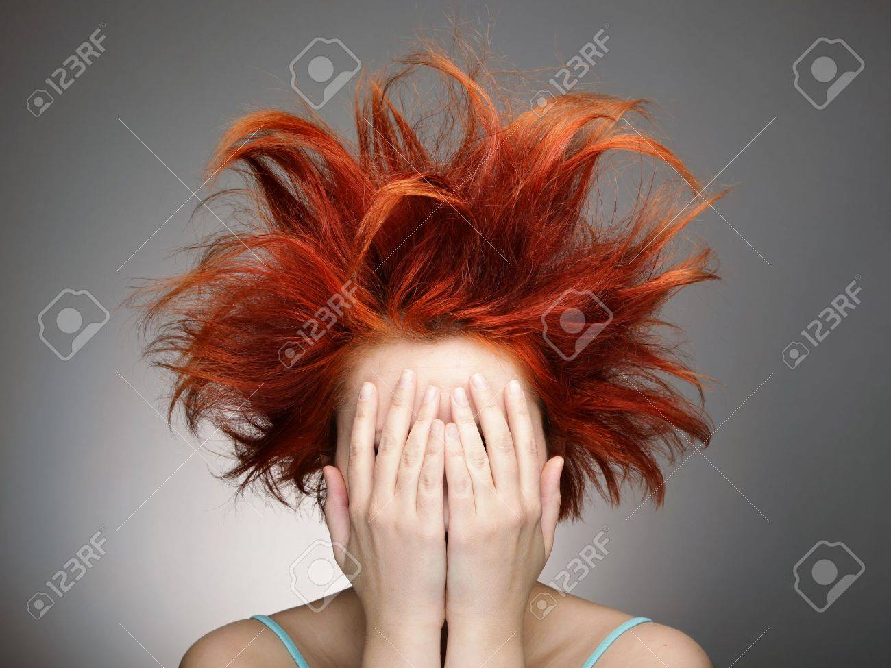 Redhead with messy hair covering her face with hands Stock Photo - 11889927