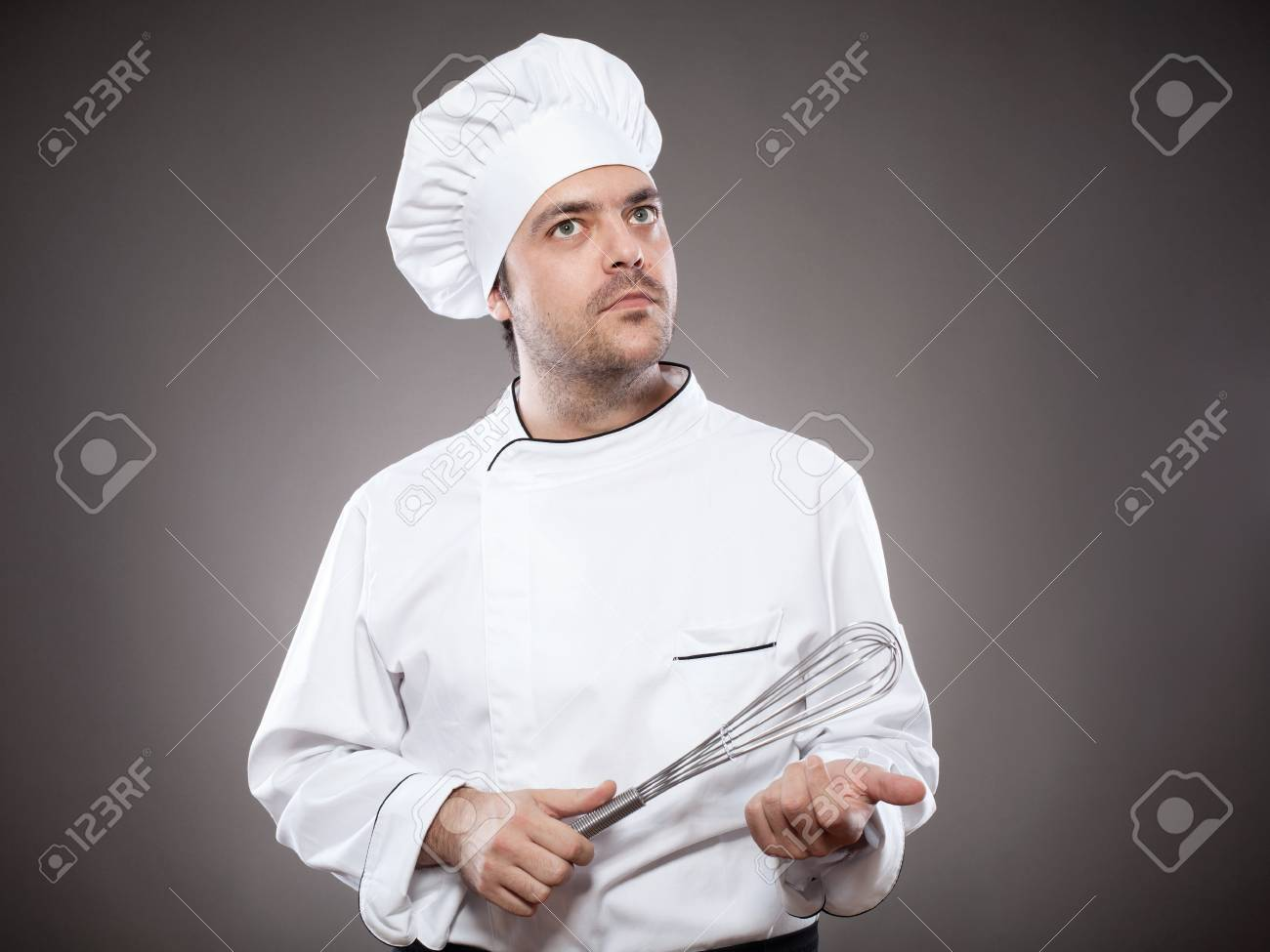 Chef with whick looking up against grey background Stock Photo - 15985411