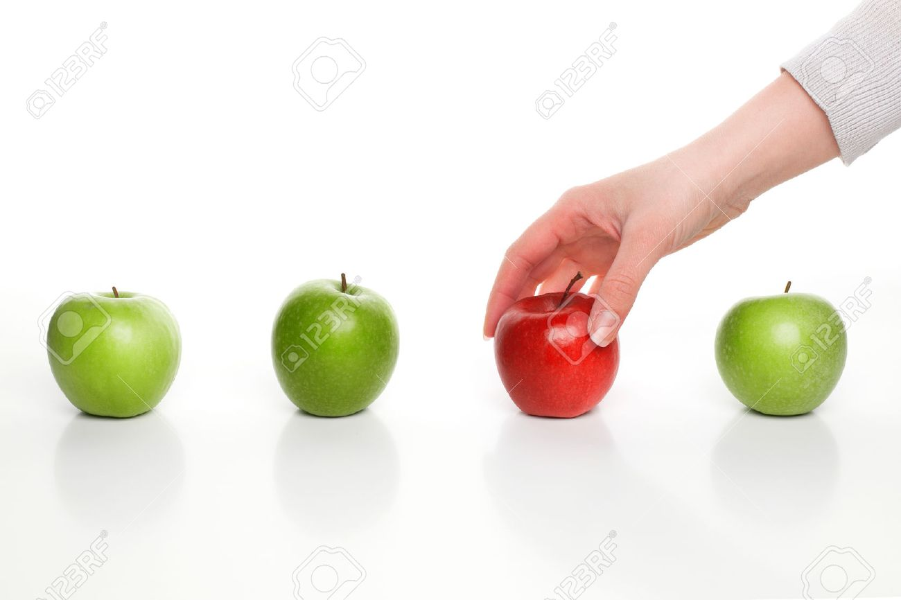 Hand picking red apple among green apples - 25410826