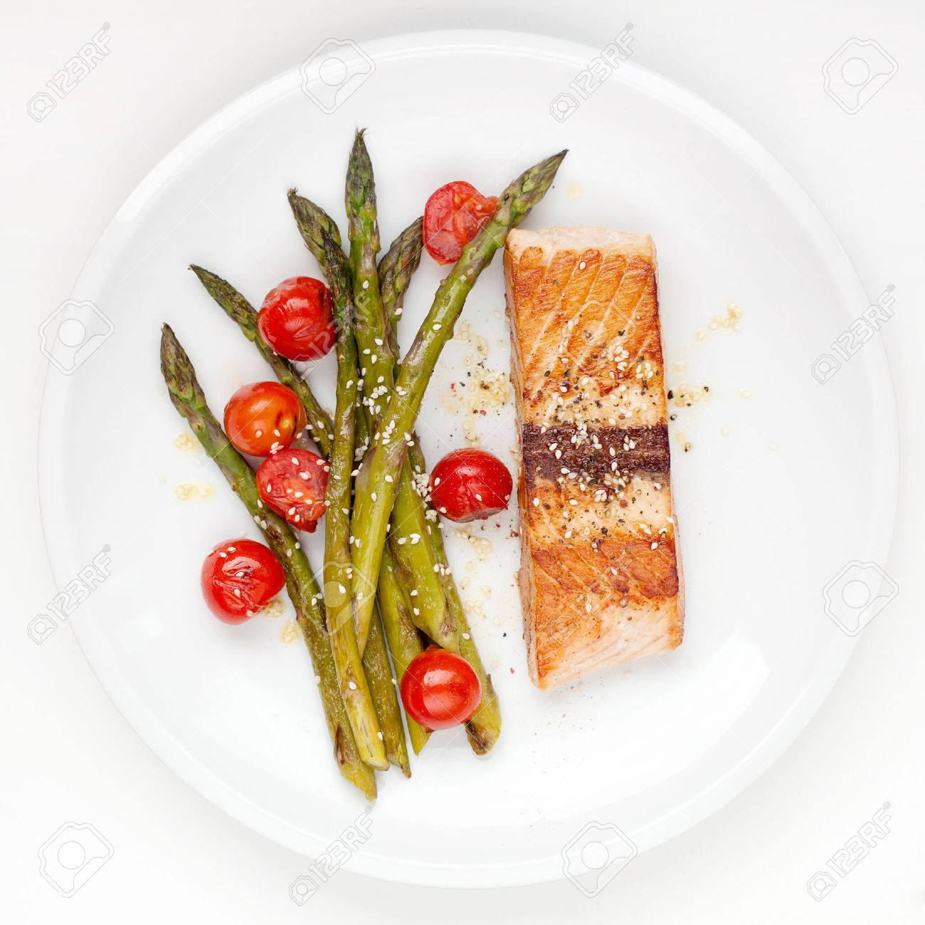 Salmon fillet with asparagus and cherry tomatoes on white plate - 27939939