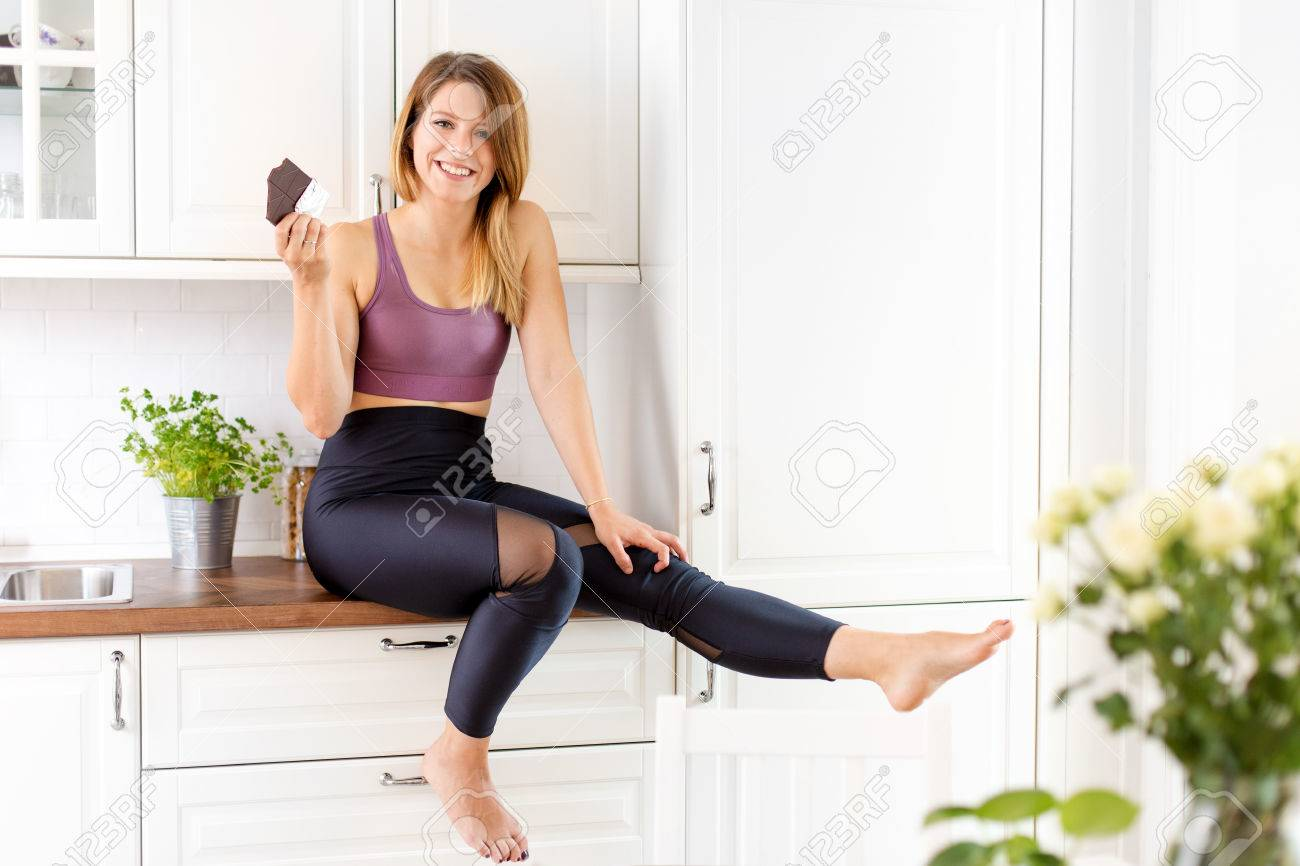 Confident young woman in her home kitchen - 87154171
