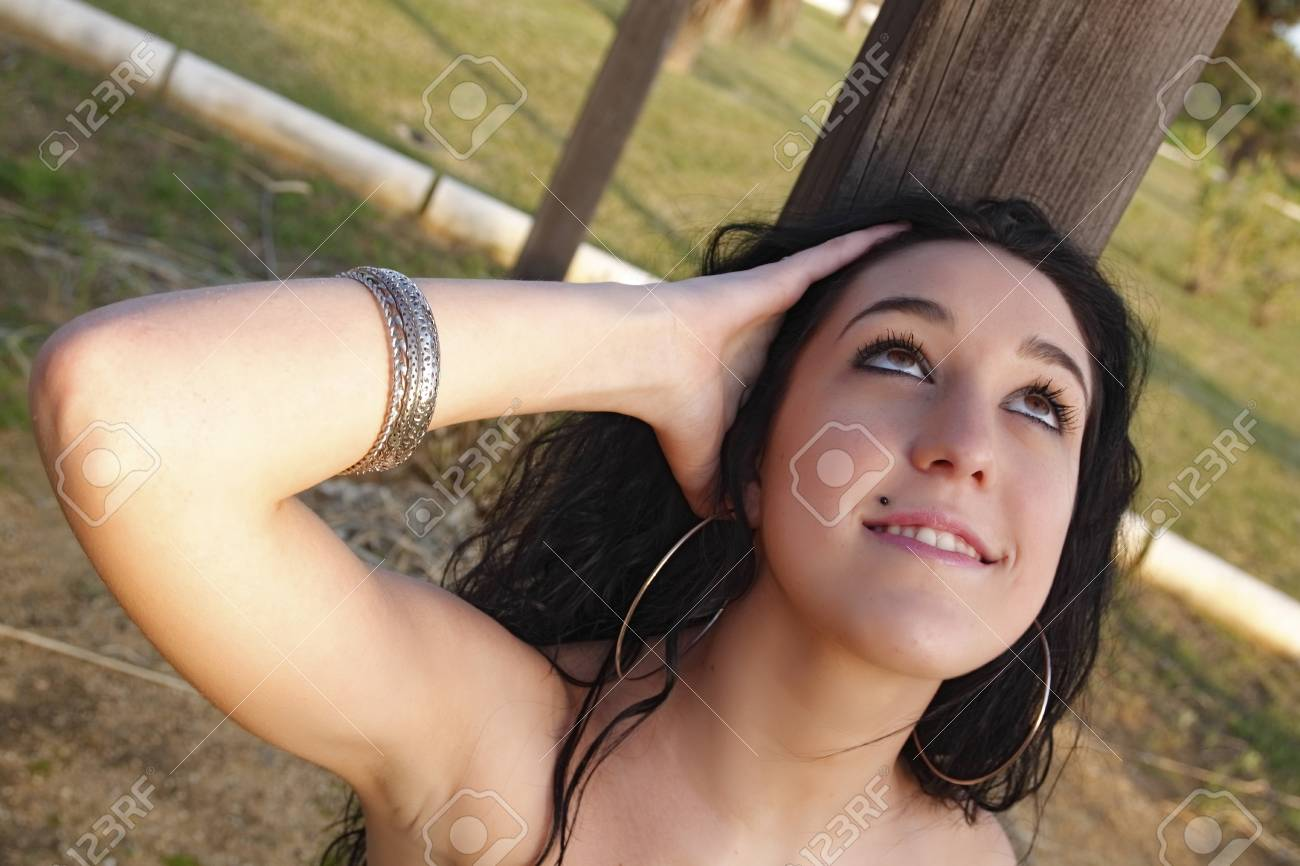 young brunette woman outdoors posing for the camera alone Stock Photo - 17009590